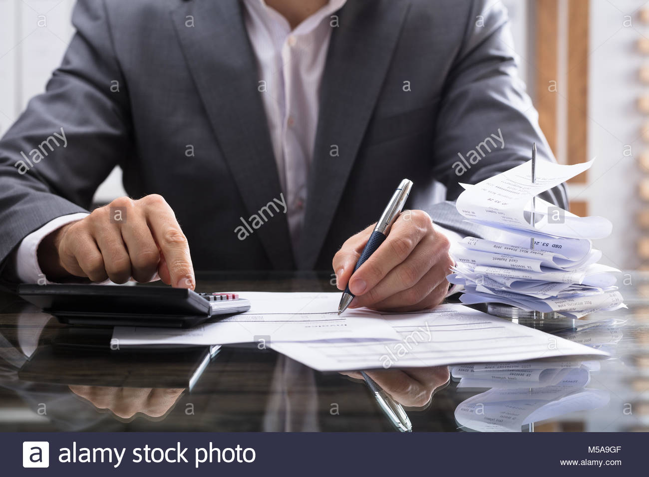 Businessperson's Hand Calculating Invoice With Calculator On Desk